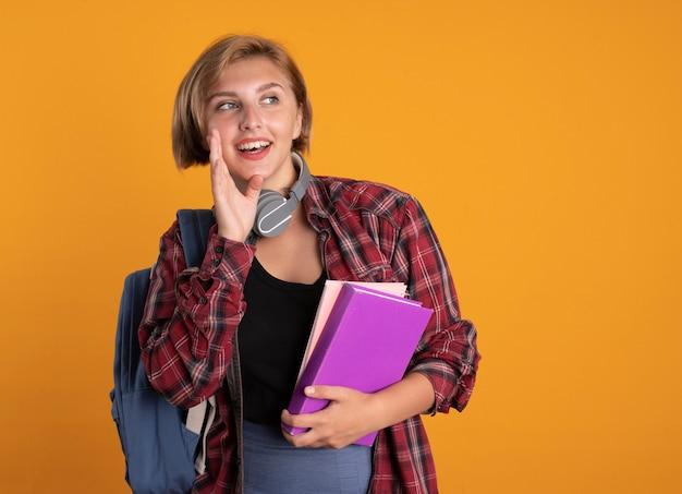 Fröhliches junges slawisches studentenmädchen mit kopfhörern, das rucksack trägt, hält die hand nah am mund, hält buch und notizbuch