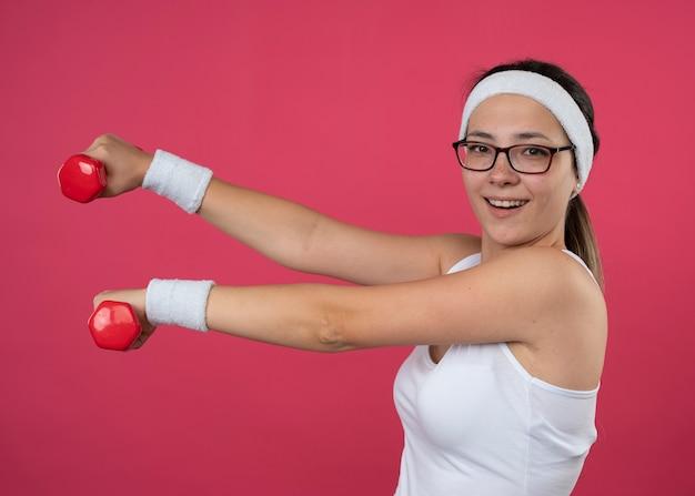 Fröhliches junges sportliches mädchen in optischer brille mit stirnband und armbändern steht seitlich mit hanteln
