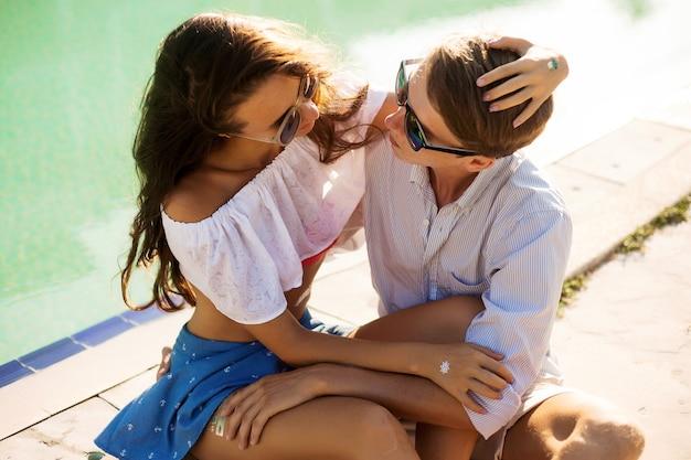 Fröhliches junges verliebtes paar, das spaß am einsamen strand zusammen hat