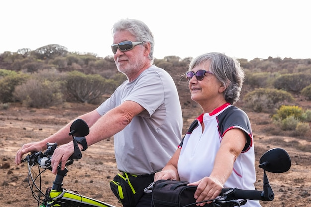 Fröhliches kaukasisches erwachsenes seniorenpaar mit mountainbike, das zusammen gesunde sportaktivitäten im freien macht - alte menschen genießen es, ältere menschen in der natur zu fahren und den lebensstil zu genießen