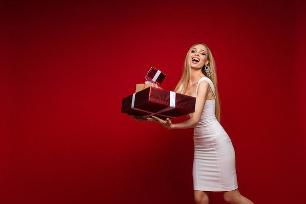 Fröhliches kaukasisches junges weibliches modell im weißen kleid mit vielen geschenken
