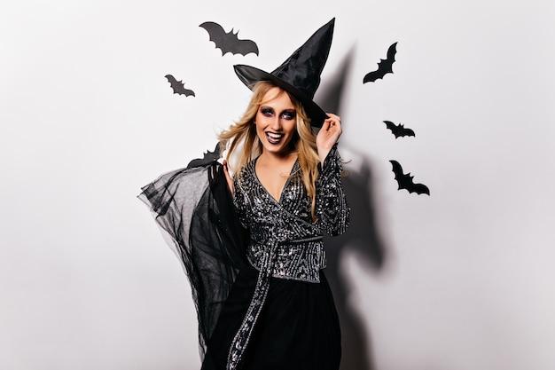 Fröhliches kaukasisches mädchen im halloween-kostüm lächelnd. hübsche frau, die im magischen hut aufwirft.