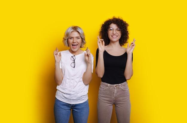 Fröhliches kaukasisches mädchen mit lockigem haar träumt von etwas in der nähe ihrer blonden freundin, während sie die finger an einer gelben wand kreuzt