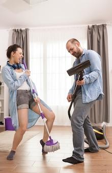Fröhliches kaukasisches paar tanzt und singt während des housekeeping and