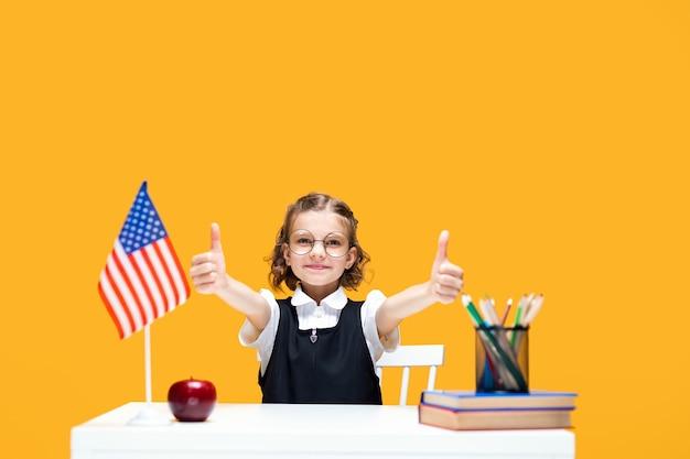 Fröhliches kaukasisches schulmädchen, das am schreibtisch sitzt und daumen hoch englischunterricht usa-flagge gestikuliert