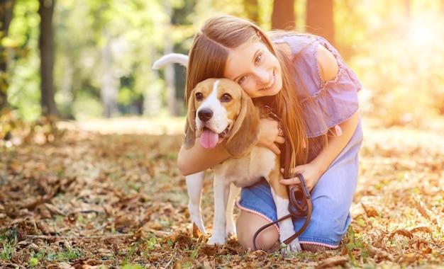Fröhliches kind, das einen hund im sommerwald umarmt