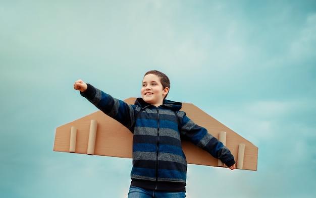Fröhliches kind, das mit papierflügelflugzeug spielt. konzept des tourismus