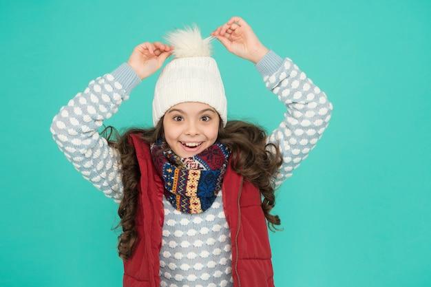 Fröhliches kind in warmer winterkleidung aus gestricktem hutschal und pullover an neujahrsferien, glückliche kindheit.