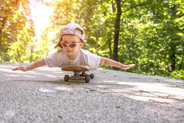 Fröhliches kind mit sonnenbrille und mütze, das auf einem skateboard in einem park liegt