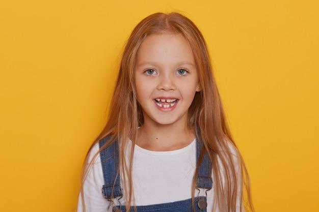 Fröhliches kind ohne vorderzähne posiert mit geöffnetem mund und lustigem lächeln.
