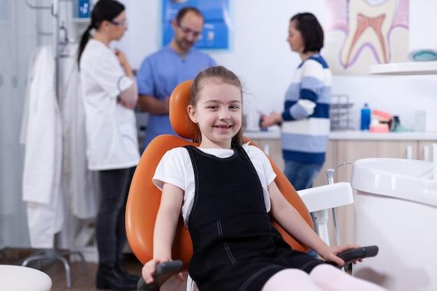 Fröhliches kind sitzt auf dem stuhl in der zahnarztpraxis während des besuchs wegen schlechter zahnbehandlung und eltern diskutieren mit dem arzt. kind mit ihrer mutter während der zahnkontrolle mit dem stomatolog, der auf dem stuhl sitzt.