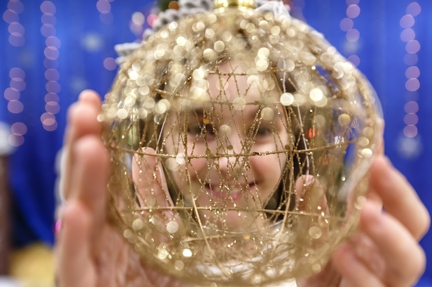 Fröhliches kleines 10-jähriges mädchen, das die kamera durch einen weihnachtsball in einem dekorierten zuhause betrachtet
