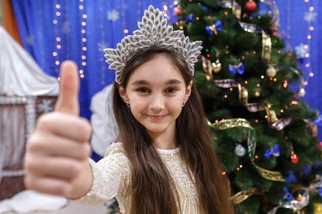 Fröhliches kleines 10-jähriges mädchen zeigt daumen hoch zeichen ok mit blick auf die kamera im weihnachtlich dekorierten haus