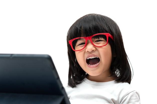 Fröhliches kleines asiatisches vorschulmädchen mit roter brille und tablet-pc auf weißem hintergrund und lachen, asiatisches mädchen, das mit einem videoanruf mit tablet lernt, bildungskonzept für schulkinder