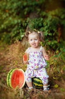 Fröhliches kleines baby, das auf einer wassermelone sitzt. das konzept von lebensstil und gesunder ernährung