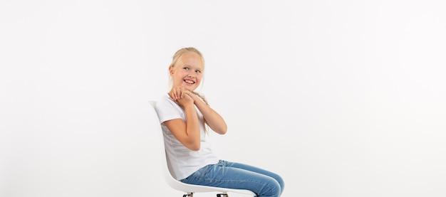 Fröhliches kleines blondes kindermädchen, das auf dem stuhl mit dem lächeln lokalisiert auf weißem hintergrund mit kopienraum sitzt.
