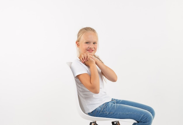 Fröhliches kleines blondes kindermädchen, das auf dem stuhl mit dem lächeln lokalisiert auf weißem hintergrund sitzt.