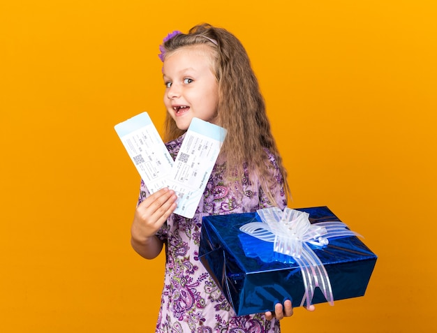 Fröhliches kleines blondes mädchen, das geschenkbox und flugtickets isoliert auf oranger wand mit kopierraum hält