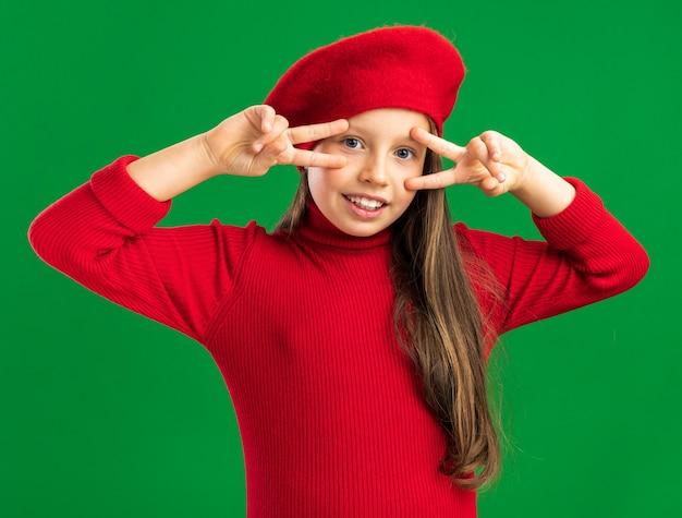 Fröhliches kleines blondes mädchen mit rotem barett, das ein vsign-symbol in der nähe der augen zeigt, die nach vorne isoliert auf grüner wand schauen