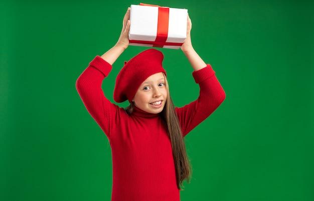 Fröhliches kleines blondes mädchen mit rotem barett, das geschenkpaket über dem kopf hält und auf die kamera schaut, die auf grüner wand mit kopienraum isoliert ist?