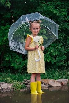 Fröhliches kleines emotionales mädchen mit transparentem regenschirm im gelben kleid und regenstiefeln im parksommer