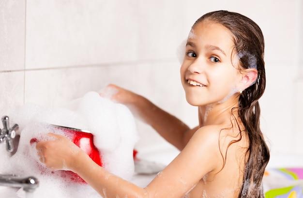Fröhliches kleines kaukasisches mädchen spielt mit schaum beim baden in der badewanne