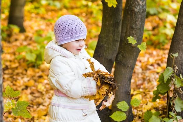 Fröhliches kleines kind, baby, das im herbst auf dem naturspaziergang im freien lacht und spielt