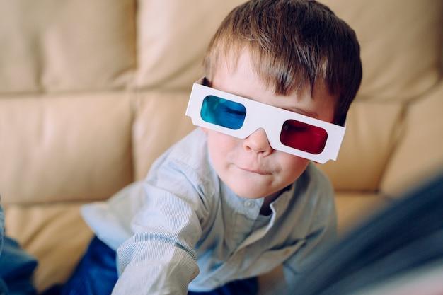 Fröhliches kleines kind, das mit dreidimensionaler brille und interaktivem kino zu hause spielt. freizeit- und filmkonzept.