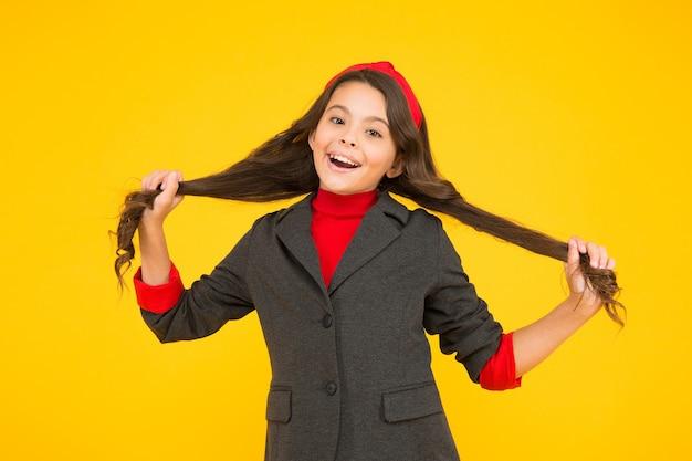 Fröhliches kleines kind in schuluniform hält langes brünettes haar sperrt gelben hintergrund, salon.