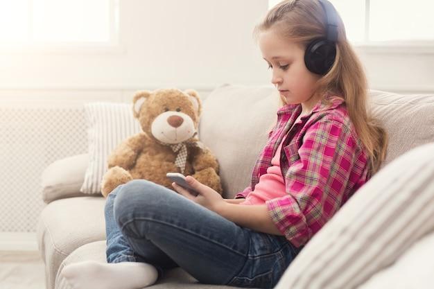 Fröhliches kleines lässiges mädchen in kopfhörern, das musik auf dem smartphone hört. hübsches kind zu hause, das cartoon auf dem handy online sieht, mit ihrem teddybären auf dem sofa sitzt, platz kopieren