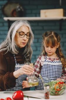 Fröhliches kleines mädchen, das beim kochen spaß mit der alten oma im ruhestand hat