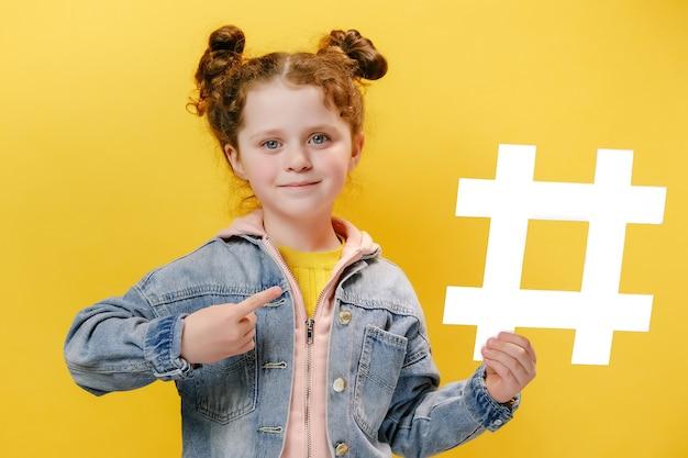Fröhliches kleines mädchen, das einen weißen hashtag hält und darauf auf gelbem hintergrund zeigt