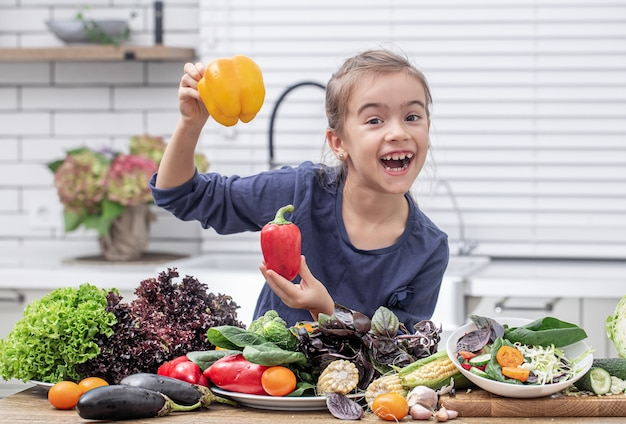 Fröhliches kleines mädchen, das paprika auf einem hintergrund des verschiedenen gemüses hält. gesundes lebensmittelkonzept.