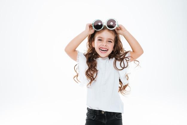 Fröhliches kleines mädchen, das runde sonnenbrille hält und lacht