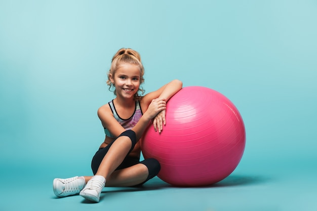 Fröhliches kleines mädchen, das sportkleidung trägt, die sich auf einen fitnessball stützt, der über blauer wand lokalisiert wird