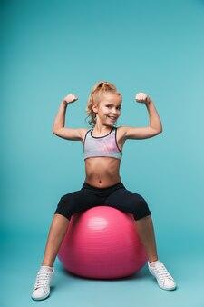Fröhliches kleines mädchen, das sportkleidung trägt, die übungen mit fitnessball lokalisiert über blauer wand tut