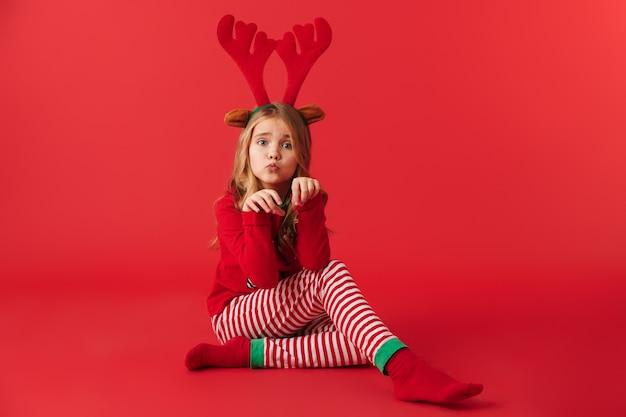 Fröhliches kleines mädchen, das weihnachts-rentierkostüm trägt, das isoliert sitzt