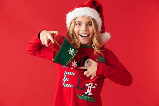Fröhliches kleines mädchen, das weihnachtskostüm trägt, das isoliert steht und geschenke von einer weihnachtssocke nimmt