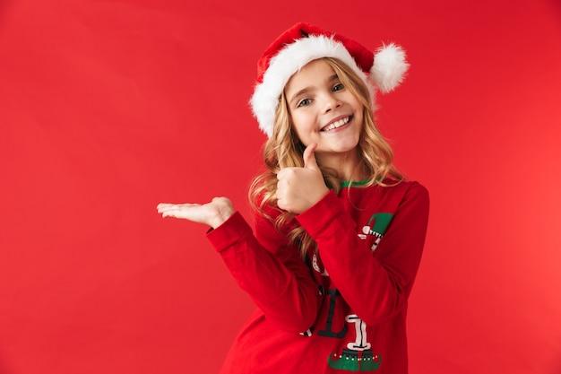 Fröhliches kleines mädchen, das weihnachtskostüm trägt, das isoliert steht und kopienraum präsentiert