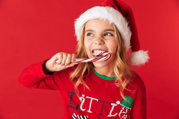 Fröhliches kleines mädchen, das weihnachtskostüm trägt, das isoliert steht und weihnachtsbonbonkegelbonbon isst