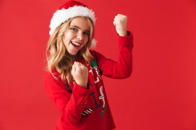 Fröhliches kleines mädchen, das weihnachtskostüm trägt, das isoliert steht