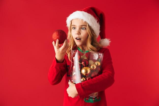 Fröhliches kleines mädchen, das weihnachtskostüm trägt, das lokal steht und satz weihnachtsbaumspielzeug hält
