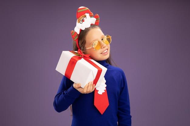 Fröhliches kleines mädchen in blauem rollkragenpullover mit roter krawatte und lustigem weihnachtsrand auf dem kopf, der ein geschenk hält, das fasziniert über lila wand steht