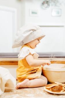Fröhliches kleines mädchen in einer weißen kappe bereitet teig mit einem schneebesen in einem teller mehl vor, der auf dem tisch sitzt