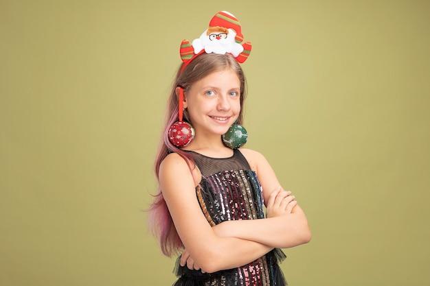 Fröhliches kleines mädchen in glitzer-partykleid und stirnband mit weihnachtsmann mit weihnachtskugeln auf den ohren mit blick in die kamera lächelnd auf grünem hintergrund stehend