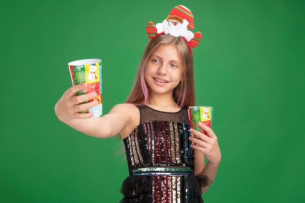 Fröhliches kleines mädchen in glitzer-partykleid und weihnachtsmann-stirnband, das zwei bunte pappbecher hält und sie fröhlich lächelnd über grünem hintergrund anschaut