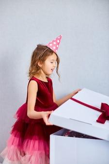 Fröhliches kleines mädchen in rosa kleid und hut öffnen große geschenkbox mit luftballons zu hause geburtstagsparty-streamer, alles gute zum geburtstag. feiern