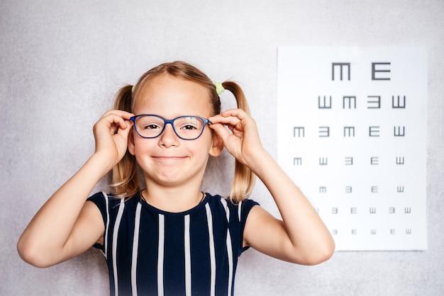 Fröhliches kleines mädchen mit brille, das vor der schule einen sehtest mit verschwommener sehtafel im hintergrund, kindergarten und schulmedizinischer untersuchung macht