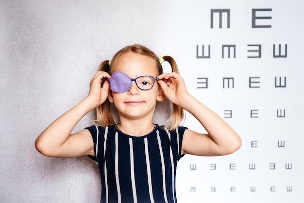 Fröhliches kleines mädchen mit brille und augenklappe oder okkluder mit verschwommenem sehtestdiagramm im hintergrund, amblyopie-behandlung (faules auge), sehtest zu hause