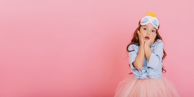 Fröhliches kleines mädchen mit dem langen brünetten haar in der prinzessinnenmaske, die auf kamera lokalisiert auf rosa hintergrund erstaunt schaut. feiern sie hellen karneval für kinder, spaß haben. platz für text